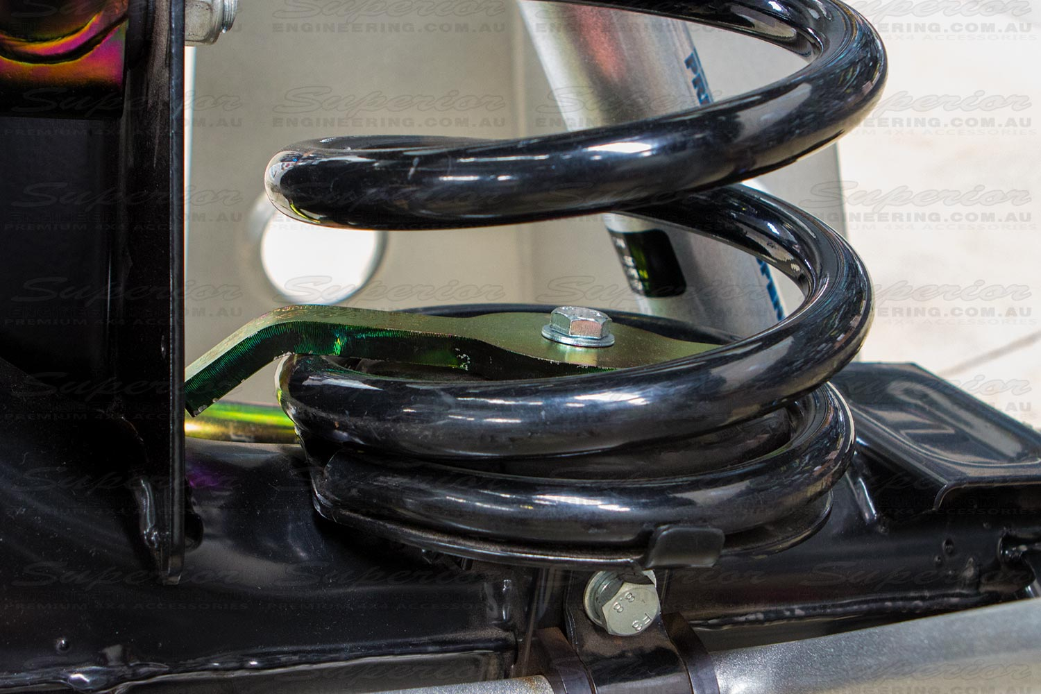 Closeup view of the heavy duty Coil Retainer installed and fitted to the chassis display diff holding down a black Superior coil spring