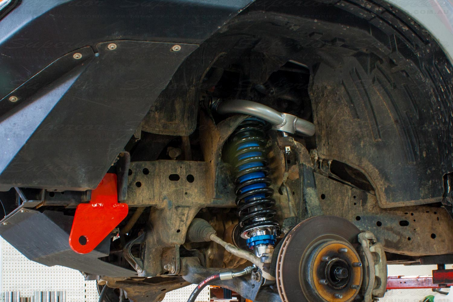 Closeup view of a single heavy duty rated towing point, upper control arm, strut and coil spring fitted to the front end of a NP300 Nissan Navara